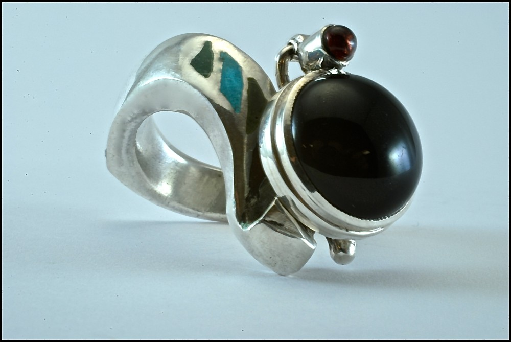 Sterling silver ring with enamel inlay and attached sterling silver pendant set with 6mm round cabochon onyx and 3mm round cabochon garnet. 2017.