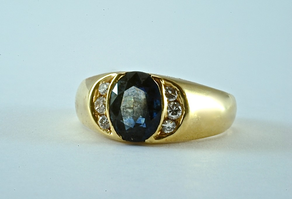 18kt yellow gold ring set with 8 x 6 oval sapphire and 6 2.5mm round diamonds. 2002.