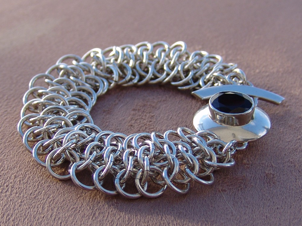 Crotalus weave bracelet, sterling silver with garnet clasp